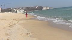 Woman running on sea beach - stock footage