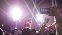 Crowd fan spectators raise hands smartphones shooting a concert in lumiere - stock footage