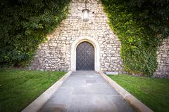 Small door at stone wall of old castle. - stock photo