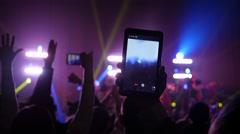 Crowd fan spectators silhouettes rais hands smartphones shooting a concert - stock footage