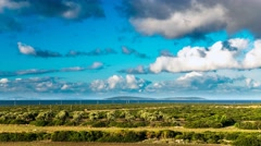 Clouds over the green field, olive trees and sea view in a distance. Timelapse - stock footage
