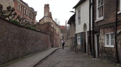 York England woman walking old home cobblestone road 4K - stock footage