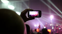 Stock Video Footage of Fan spectator shooting video via smartphone camera at concert flashing lumiere