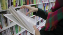 Young woman in a book store - stock footage