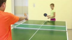 Boy and girl playing ping pong in the bright room, focus on boy Stock Footage
