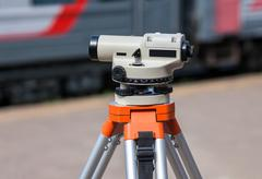 Geodetic equipment optical level mounted on tripod at the railway station - stock photo