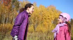 Mother and daughter gives five at walking in the forest on the rollers Stock Footage