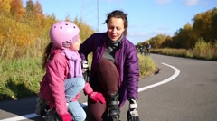 Mother helps her daughter to stand up on the rollers on the road Stock Footage