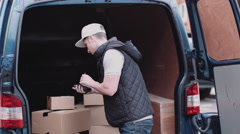 Delivery man at van scanning boxes with barcode scanner Stock Footage