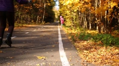 Woman on roller skates with leaf in hand on the track in the forest Stock Footage