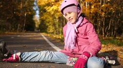A girl on roller skates and a helmet sits on the track in forest Stock Footage