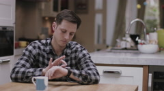 Young Adult male using smart watch at home on kitchen table - stock footage