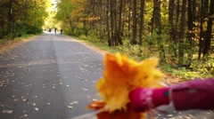 Girl roller-skating in the autumn forest with leaves in hand Stock Footage