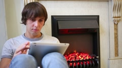 A young man looking at the tablet at fireplace in the living room Stock Footage