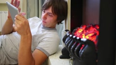 A man with a tablet in hands lying on the floor next to the fireplace Stock Footage