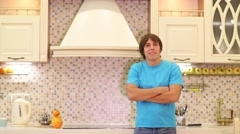 Young man standing in the kitchen with arms crossed Stock Footage