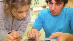 The man and the girl look into a tablet at the table Stock Footage
