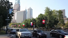 Cars moving on the Benjamin Franklin Parkway against of skyscrapers Stock Footage