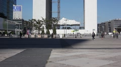 People walk near La Grande Arche de la Defense in business centre Stock Footage