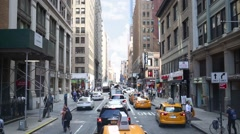 Traffic in New York City at 30th street, cars pass pedestrians Stock Footage