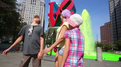 Mother with two children stands at Love sculpture and green fountain Stock Footage