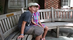 Girl and boy sitting on a bench, smile and nod their heads Stock Footage