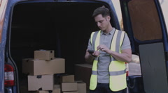 Delivery man scanning boxes with barcode scanner Stock Footage