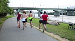 A group of young people during jogging on the embankment Stock Footage