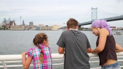 Family looking at the Delaware River on the waterfront Stock Footage