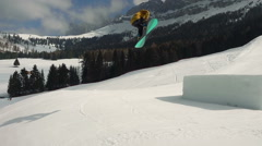 Professional snowboarder doing frontside on kicker slow motion Stock Footage