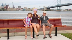 Mother with children sits on bench on the Delaware River embankment Stock Footage