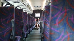 Boy and girl sitting in the back seat of an empty bus Stock Footage