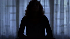 Woman in yoga pose in a dark room seems to be reproaching herself Stock Footage