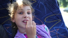 Girl sitting in the bus with the earpiece in ear and snacking Stock Footage