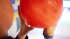 Boy throws an orange ball on the track in bowling club - stock footage