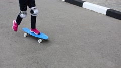 The girl in pink sneakers and knee pads jumps from the skateboard Stock Footage