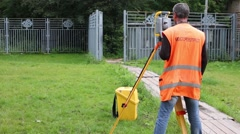 Mosgorgeotrest employee takes measurements near a metal fence Stock Footage