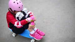 Girl sitting on a skateboard and hugging her knees Stock Footage