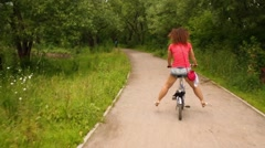 A woman riding a bicycle with her legs apart to the sides Stock Footage