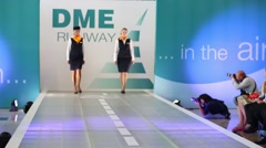 Two girls demonstrates uniform of the Lufthansa at the fashion show Stock Footage