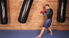 Young man training with a punching bag in the hall of mixed martial arts. - stock footage