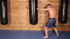 Young man training with a punching bag in the hall of mixed martial arts. Stock Footage