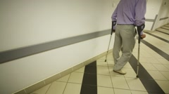 A man walks along the clinic corridor leaning on a walking sticks Stock Footage
