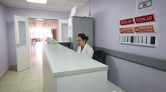 A woman sits at a table in the clinic and answers the phone. Stock Footage