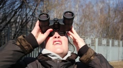 A woman looks at Solar eclipse of March 20, 2015 through binoculars Stock Footage