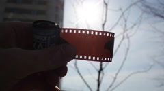 Hand of man which looks solar eclipse through photographic film Stock Footage