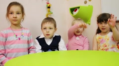 Four children sits at table and shows gesture OK in school Stock Footage