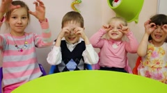 Four kids puts their hands to face portraying glasses Stock Footage