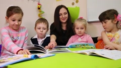 A teacher and children look at a textbook, teacher points in the book Stock Footage