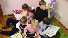 Six children sit on the floor in a circle with textbooks in hands Stock Footage
